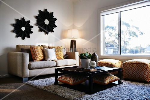 Quadratischer couchtisch vor sofa mit gemusterten kissen und polsterhockern mit gleichem muster - Sofa vor fenster ...