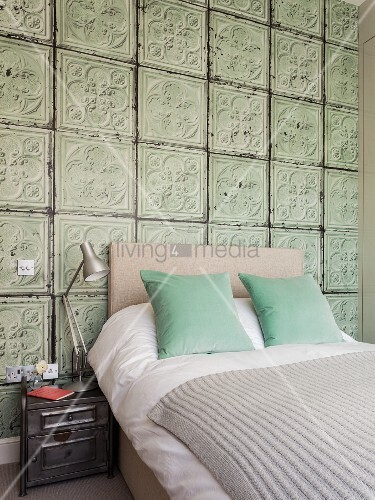 Double bed with headboard against wall covered in old 3D structured tiles in bedroom