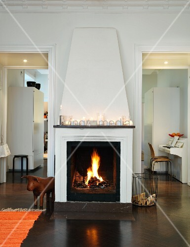 Lanterns on mantelpiece above fire in open fireplace flanked by open doors