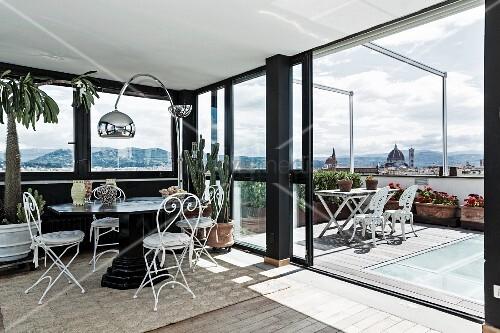 Wintergarten Auf Dachterrasse sitzplatz mit filigranen weissen metallstühlen und bogenle in