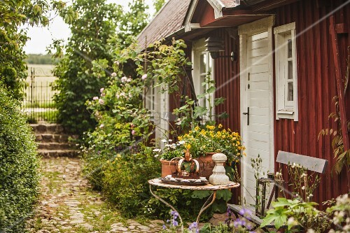 Potted plants on garden table outside simple wooden house