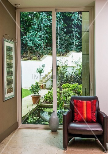 Dark brown leather armchair with red striped satin cushion in front of sliding glass door with view of garden