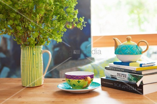 teetasse neben teekanne auf b cherstapel und keramikkrug mit frauenmantel bild kaufen. Black Bedroom Furniture Sets. Home Design Ideas