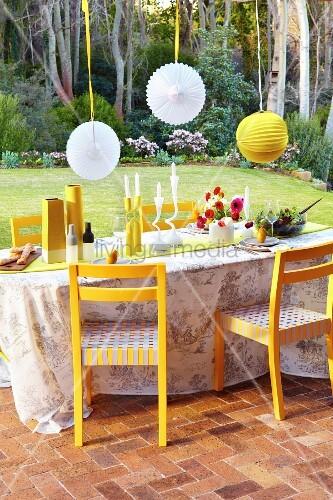 Festive terrace table below suspended lanterns