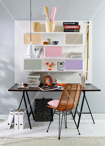 A self-designed home office – a black table in front of a white, mass-produced panel set with shelves and coloured boxes and a retro wicker chair with a black metal frame