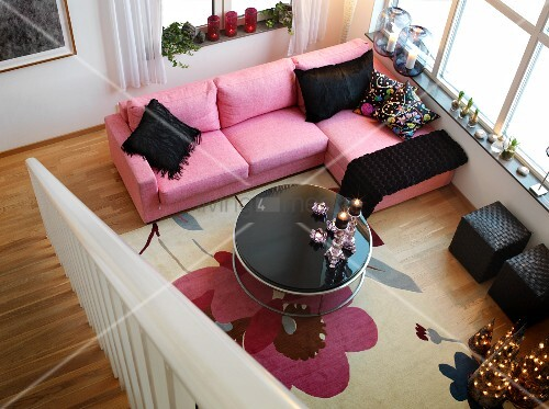 View from landing down into living room with pastel pink sofa, black accessories and Advent candle arrangement