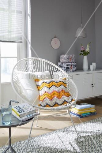 Kissen mit selbstgehäkeltem Bezug in weißem Retro Sessel vor Sideboard an hellgrauer Wand