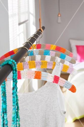 Bunte, gehäkelte Bezüge mit Blockstreifen für Kleiderbügel auf Kleiderstange