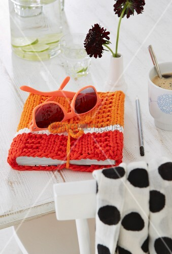 A pair of sunglasses on a knitted book cover in red and orange tones on a white cloth