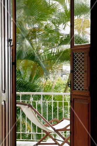 View of deckchair and palm trees in courtyard through balcony doors