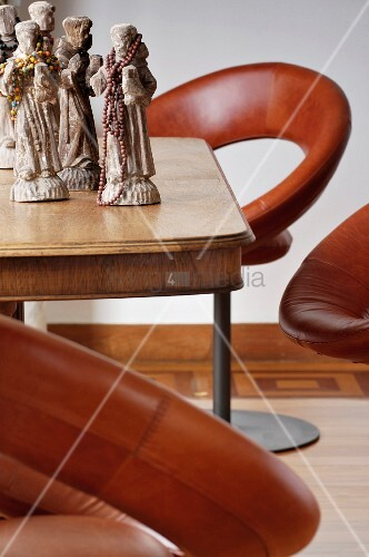 Brown leather swivel chairs around collection of stone figurines, some decorated with beads, on simple wooden table
