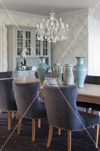 Chairs with blue velvet upholstery at long, pale wood dining table with collection of vases below crystal chandelier in traditional interior