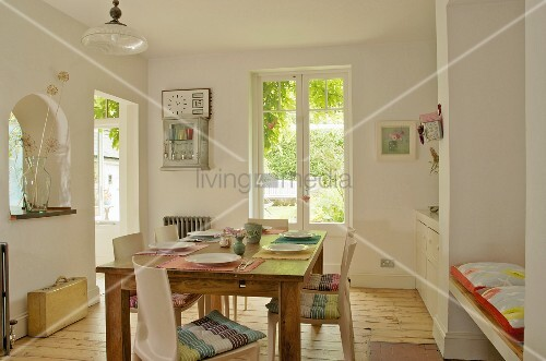 Friendly dining room with set table in centre; fitted shelving and bench in niches
