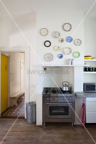 Various ornamental wall plates above stainless steel gas cooker in disused fireplace niche of period-apartment kitchen; view into hallway with yellow door