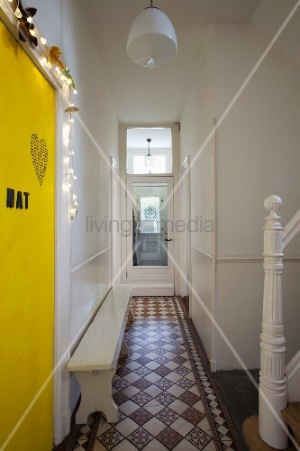 Rustic wooden bench on original tiled floor in hallway of Dutch house; newel post of old staircase and yellow-painted door with decorative letters