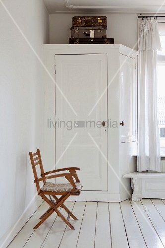 Vintage suitcases on original fitted wardrobe and wooden folding chair in bedroom with white wooden floor