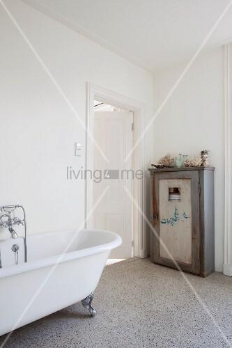 Rechts Von Der Badezimmertür Ein Vintage Schrank, Links Davon Eine Freistehende  Wanne Mit Klauenfüssen Und Retroarmatur