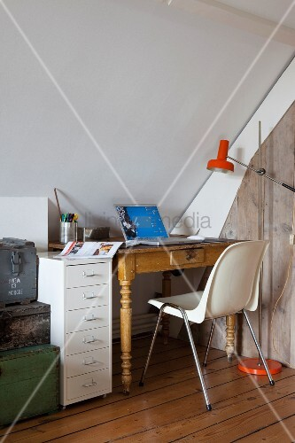 Small, eclectic workspace under sloping ceiling with antique table, shell chair, modern filing cabinet and stack of old trunks