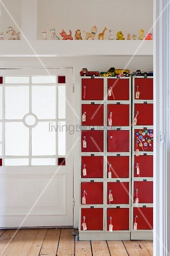 Toy cars on top of eye-catching locker cabinet with red doors in hallway with beautiful lattice door and row of squeaky toys on roof beam