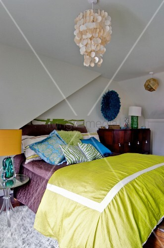Capiz shell pendant lamp above bed with many scatter cushions and green bedspread in attic bedroom