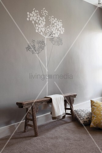 Rustic wooden bench against pale grey wall with tree mural in grey and white