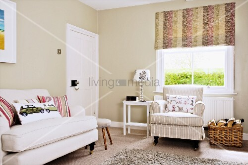 White couch and armchair in front of window with roller blind in living room