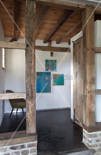 Durchgang Zwischen Fachwerkstützen Mit Blick In Flurbereich Mit Rustikaler  Holzdecke Und Modernen Bildern