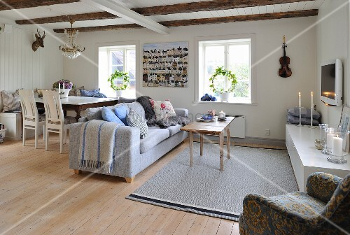 Dining area and seating area with sofa in open-plan interior with wooden walls and exposed ceiling beams