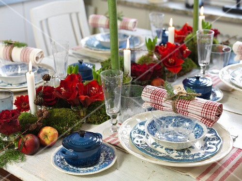 Blue and white place setting with napkin and amaryllis centrepiece on table set for Christmas dinner