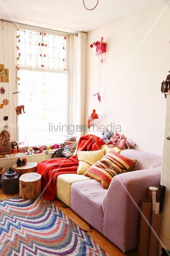 Lounge area in shades of red and pink with tree-stump table, woven rug, knick-knacks, Indian souvenirs and cuckoo clock