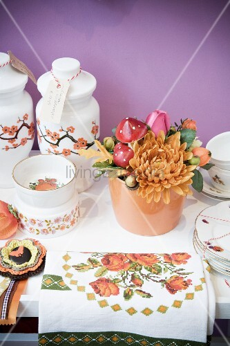 Flower arrangement with accessories, vases and crockery on surface