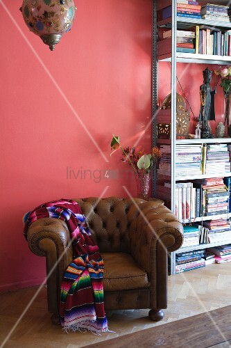 Eclectic ambiance with traditional leather armchair and ethnic blanket in front of metal bookcase against pink wall