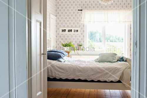 Bed with white lace bedspread in rustic interior