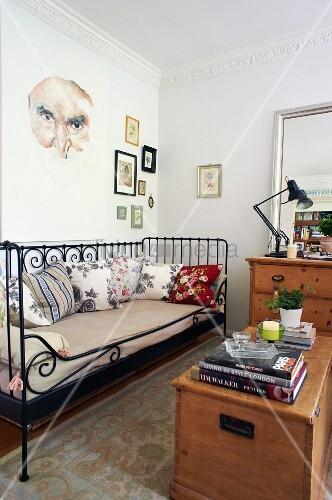 Wooden trunk opposite black, vintage metal daybed in living room