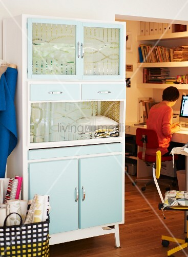 Pastel-coloured fifties cupboard with glass door panels; view of person sitting at desk to one side
