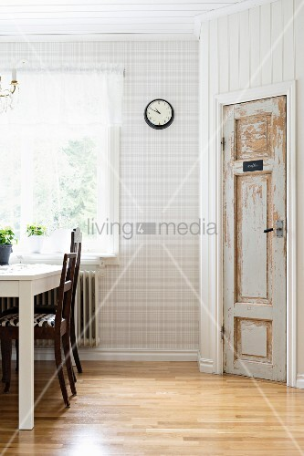 Dining set below window, glossy parquet floor and vintage interior door in wood-panelled, angled wall