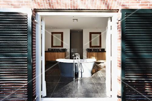 Blick durch offene Tür mit dunklen Türläden auf freistehende Badewanne mit Standarmatur in grossräumigem Bad