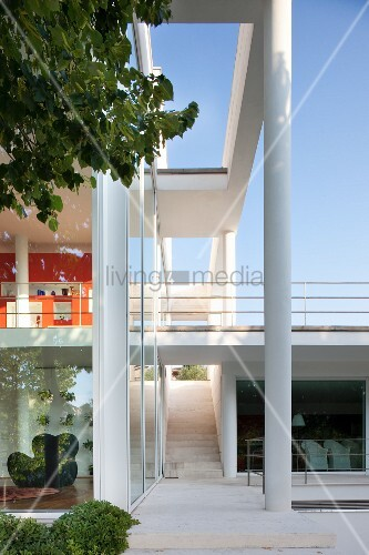 Glasfassade eines zeitgenössischen Wohnhauses, davor Stütze und Vordach, im Hintergrund Terrasse