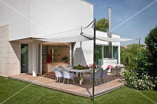 Holzdeck mit Sonnensegel über Terrasse mit hellen Kunststoff Stühlen, vor zeitgenössischem Wohnhaus