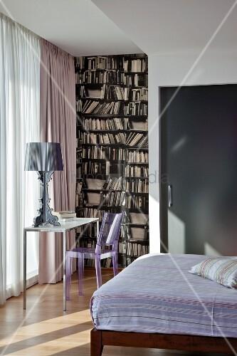 Designerlampe auf kleinem Tisch und Kunststoff Stuhl vor bodenlangem Vorhang am Fenster, seitlich Designertapete mit Bücherregal-Motiv