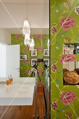 Waschbecken mit Standarmatur vor vollflächigem Wandspiegel in Designerbad mit Blumentapete