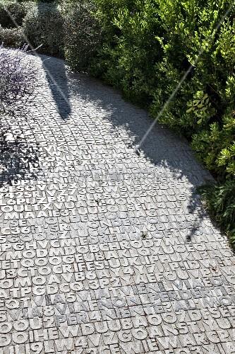 Gartenweg-Belag mit Zahlen- und Buchstaben-Muster