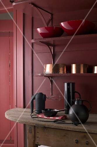 Various bowls on shelves and kitchen equipment on wooden table in Bordeaux red kitchen