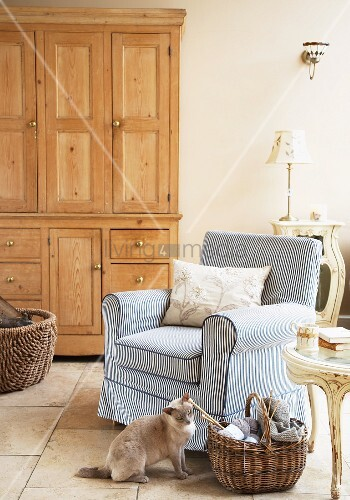 Comfortable armchair with striped cover next to knitting basket and cat sitting on floor