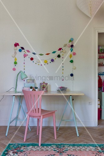 Child's desk on trestles, pink chair, colourful garlands on wall and Oriental rug on floor