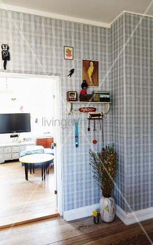 Hallway with tartan wallpaper and floor vase below bracket shelf next to open living room door
