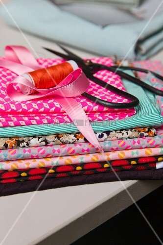 Scissors and reel of thread on top of various patterned, folded and stacked fabrics