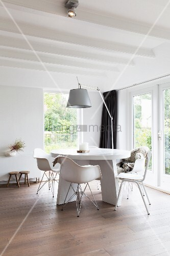Classic armchairs at white, round table and arc lamp in corner of modern living room with white, wood-beamed ceiling