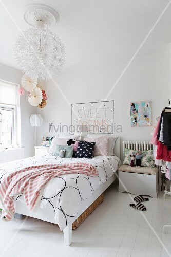 Bed linen with graphic pattern and scatter cushions on feminine bed and spherical pendant lamp in romantic bedroom
