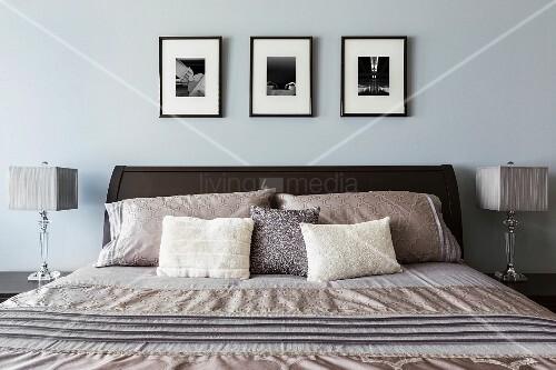 modernes schlafzimmer in blauen und silbernen farbt nen ber dem bett drei bilder in schwarz. Black Bedroom Furniture Sets. Home Design Ideas